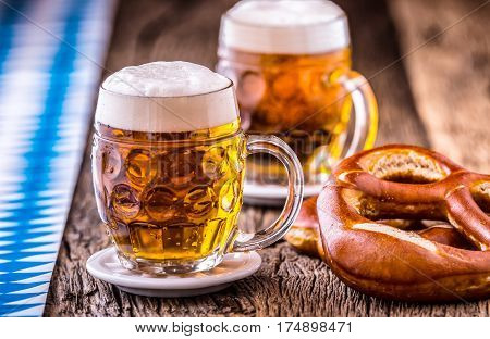 Beer. Oktoberfest.Two cold beers and pretzel. Draft beer. But draft. Golden beer. Golden however. Two gold beer with froth on top. Cold draft beer in glass jars in a hotel pub or restaurant. Still life.