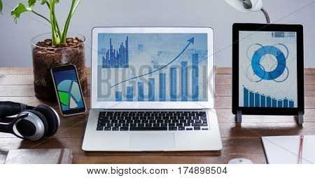 Laptop,digital tablet and mobile phone with graph charts oo wooden table