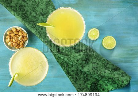 An overhead photo of lemon Margarita cocktails with wedges of lime and a salted nuts snack, on a vibrant turquoise background with copy space