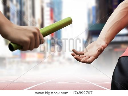 Composite image of athletes passing the baton during relay race against city buildings
