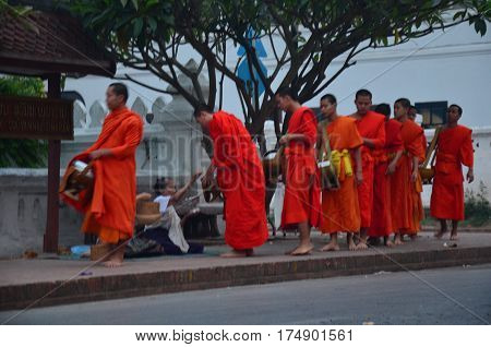 Laotian people waiting monks procession for put food offerings and almsgiving with sticky rice on the road at Wat xieng thong on April 9 2016 in Luang Prabang Laos