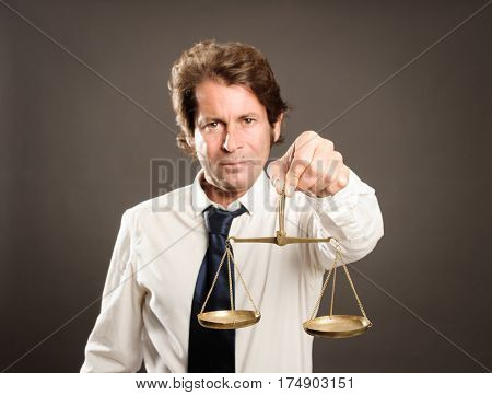 businessman holding a justice scale looking at camera