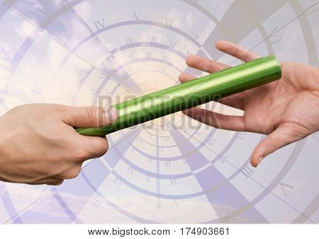 Hand of athletes passing the baton during relay race against digitally generated clock
