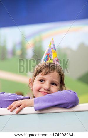 Little baby girl Celebrating her birthday. Hat and festive mood.