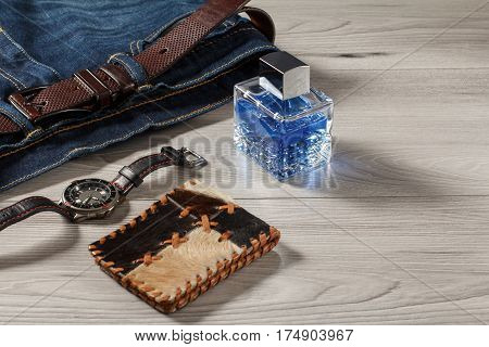 Man perfume watch with a leather strap blue jeans with leather belt and leather purse on a gray wooden background