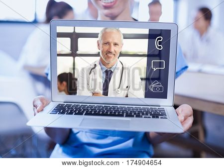 Woman holding a laptop with doctor on video call screen at clinic