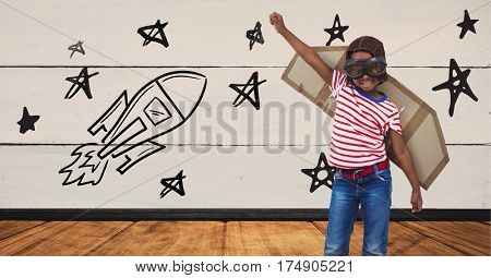 Kid pretending to be a pilot against stars and rocket drawn on wooden background