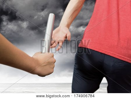 Athletes passing the baton against stormy sky in background