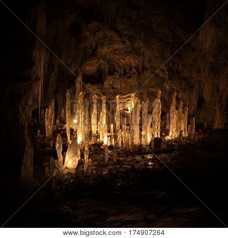 Ice stalagmites in a cave illuminated by candles