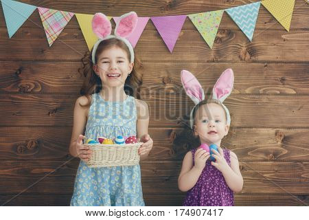 Two cute little children are wearing bunny ears at Easter day. Sisters girls are holding basket with painted eggs.