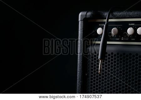 Close up of Black guitar amplifier with jack cable on black background.