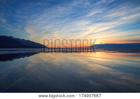 Cloudy sky and reflections in water surface with thin layer of ice on sunrise