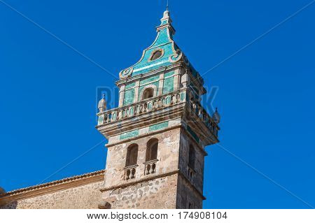 Beautiful view. Tower of the Monastery of Valldemossa in the Sierra de Tramuntana Mountains with park.