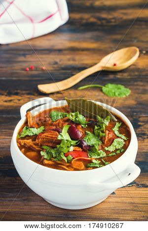 Turkey Chili. Stewed with black and white beans tomatoes bell pepper onion garlic thyme cinnamon chocolate and fresh cilantro. Soup bowl on wooden table.