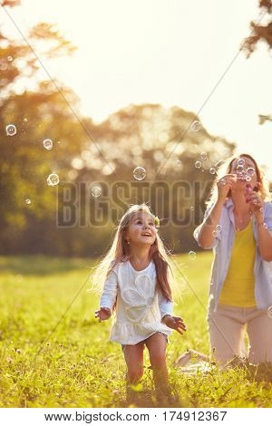 Female child chase soap bubbles outside