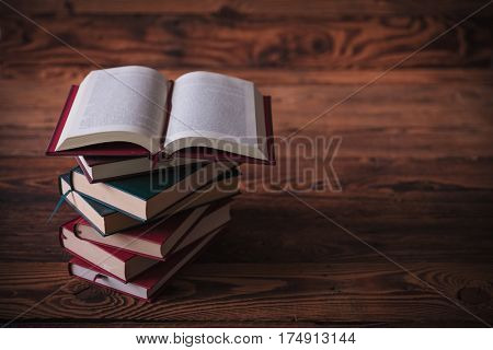 open book on top of pile of books with book sign in the middle , on old wood background, studio picture