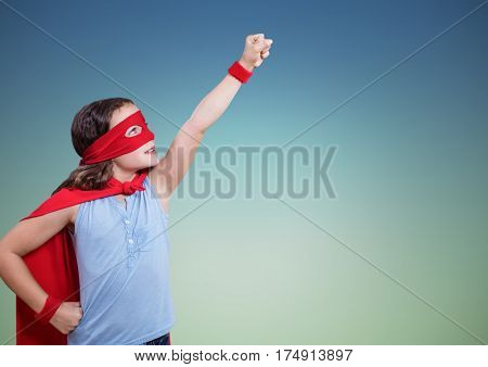 Girl in superhero costume pretending to fly against green background