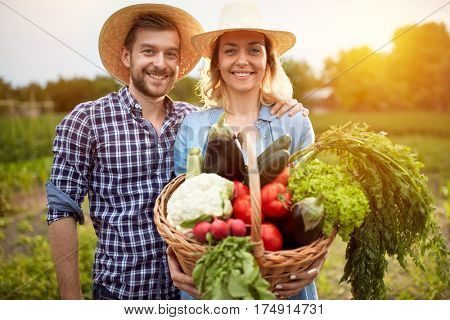 Nice farmers couple posing with basket with vegetables in nature