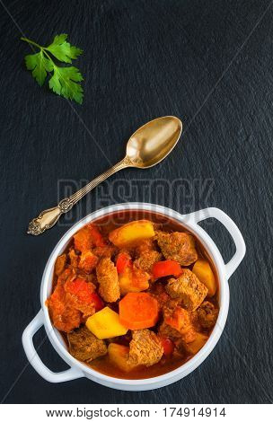 Traditional Hungarian dish goulash slow-cooked with beef potatoes carrot tomatoes paprika onion and bell peppers. White bowl on black stone background top view.
