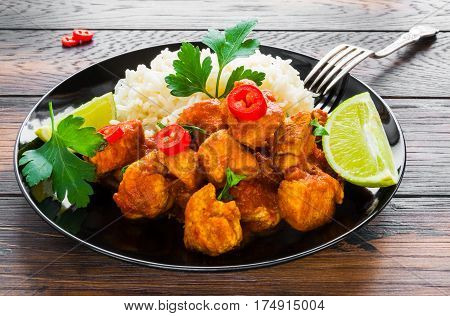 Traditional Indian dish chicken curry with fresh chilli pepper lime and parsley and boiled rice on a black ceramic plate on the wooden table.