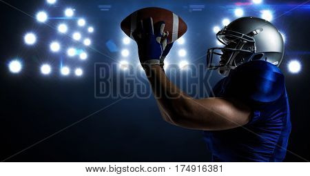 American football player catching rugby ball against stadium floodlights