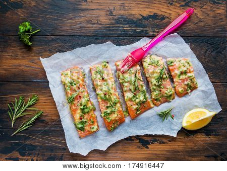 A process of cooking pieces of raw salmon have been coated by garlic herb butter mixture on parchment paper wooden table top view.