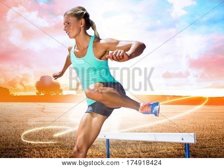 Athlete running over hurdle against digitally composite cloudy sky