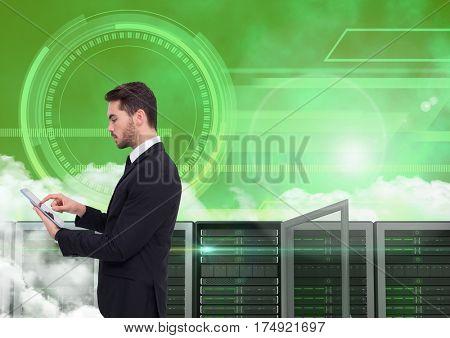 Digital composite of businessman using digital tablet against server room