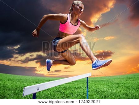 Digital composite of athlete woman jumping over hurdle against cloudy sunset