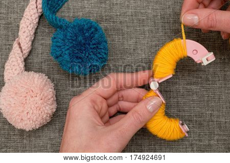 Hands Looping Yellow Yarn Around Pom-pom Maker