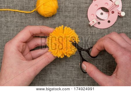 Hands Trimming A Yellow Pom-pom With Thread Scissors