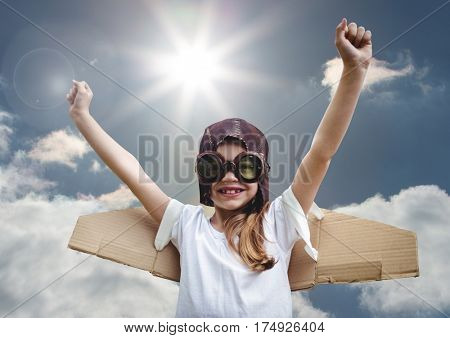 Composite image of excited smiling kid pretending to be a pilot against bright sunlight background
