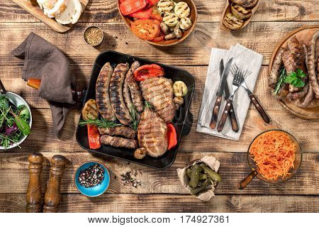 On a wooden table different food cooked on the grill. Grilled steak grilled sausages grilled vegetables on the wooden table top view