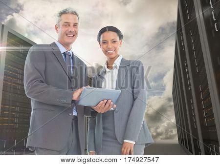 Digital composite of smiling businesspeople using digital tablet against server background