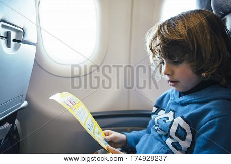 Closeup of a cute blonde boy is reading the safety airplane card while is sitting near te window at the airplane