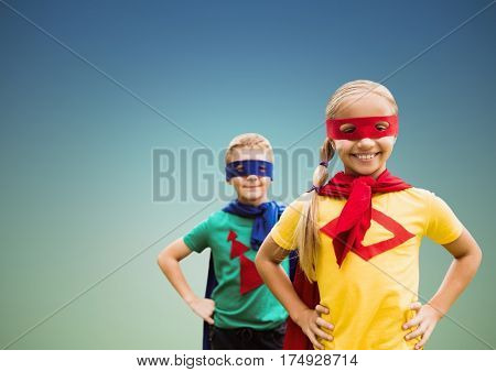 Composite image of smiling super kids in cape and mask standing with hand on hip against clear sky
