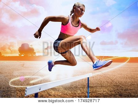 Digital composite of athlete running over hurdle in field against bright sunlight