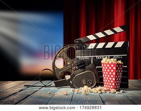 Retro film production accessories placed on wooden planks. Concept of film-making. Red curtain and movie screen on background