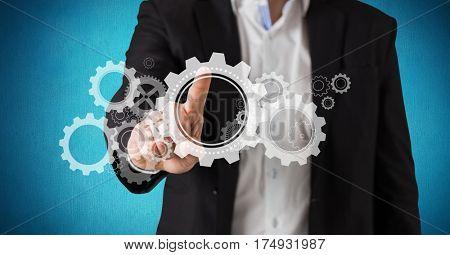 Digital composite image of businessman using old cog gear wheels against blue background