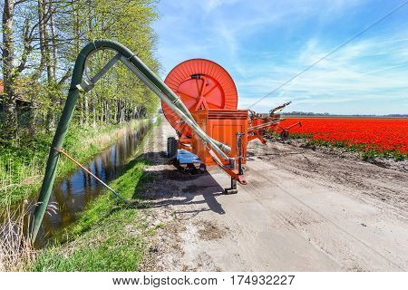 Spraying equipment on dirt road near ditch and red tulips field