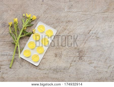 cough sore throat pastille colorful and flowers on table