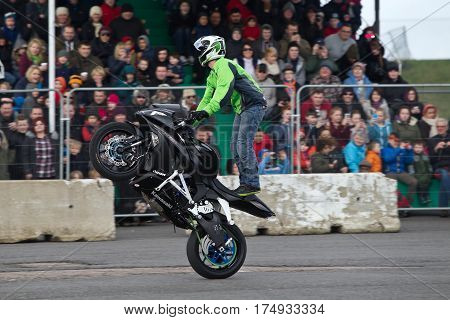 PODINGTON, UK - FEBRUARY 22: Stunt rider Lee Bowers stands on his specially modified motorcycle while demonstrating his stunt show at the Santa Pod Stuntfest show on February 22, 2014 in Podington