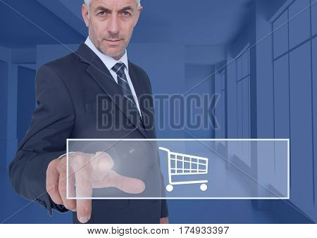 Businessman touching shopping cart icon on interface screen against digitally generated background