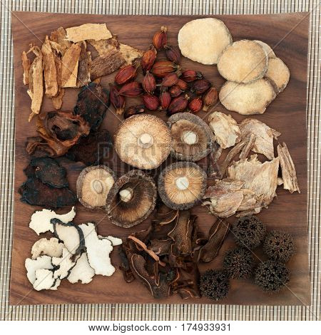 Chinese herbal medicine selection on maple wood board on bamboo background.