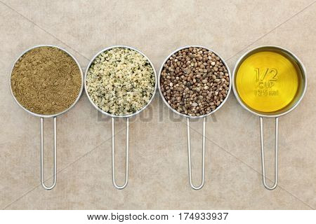Hemp health food ingredients with powder, hulled seed, dried seeds and oil in metal measuring scoops on natural hemp paper background.