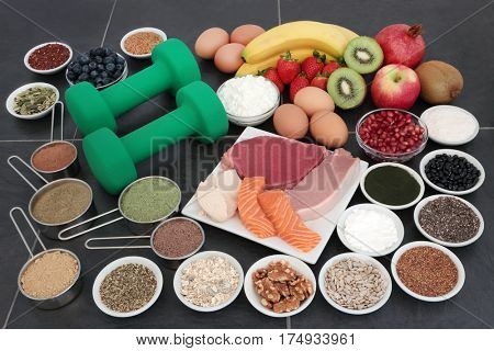 Body building dumbbell weights with food of supplement powders, high protein lean meat and salmon, fruit, dairy, nuts, seeds and grains over slate background.