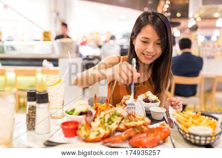 Woman enjoy her lobster in restaurant