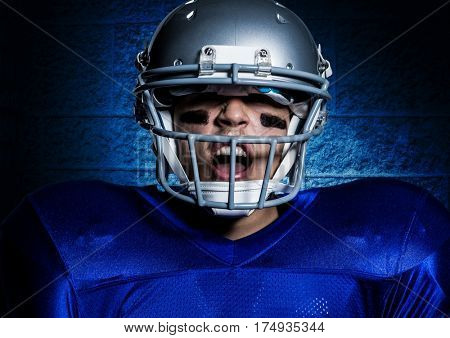 Close-up of aggressive american football player in helmet screaming against blue wall background