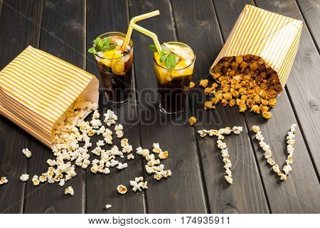 close up view of popcorn in paper containers drinks and tv lettering on table tv time concept