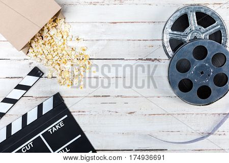 Top view of film reels popcorn and movie clapper on wooden table Movie time concept